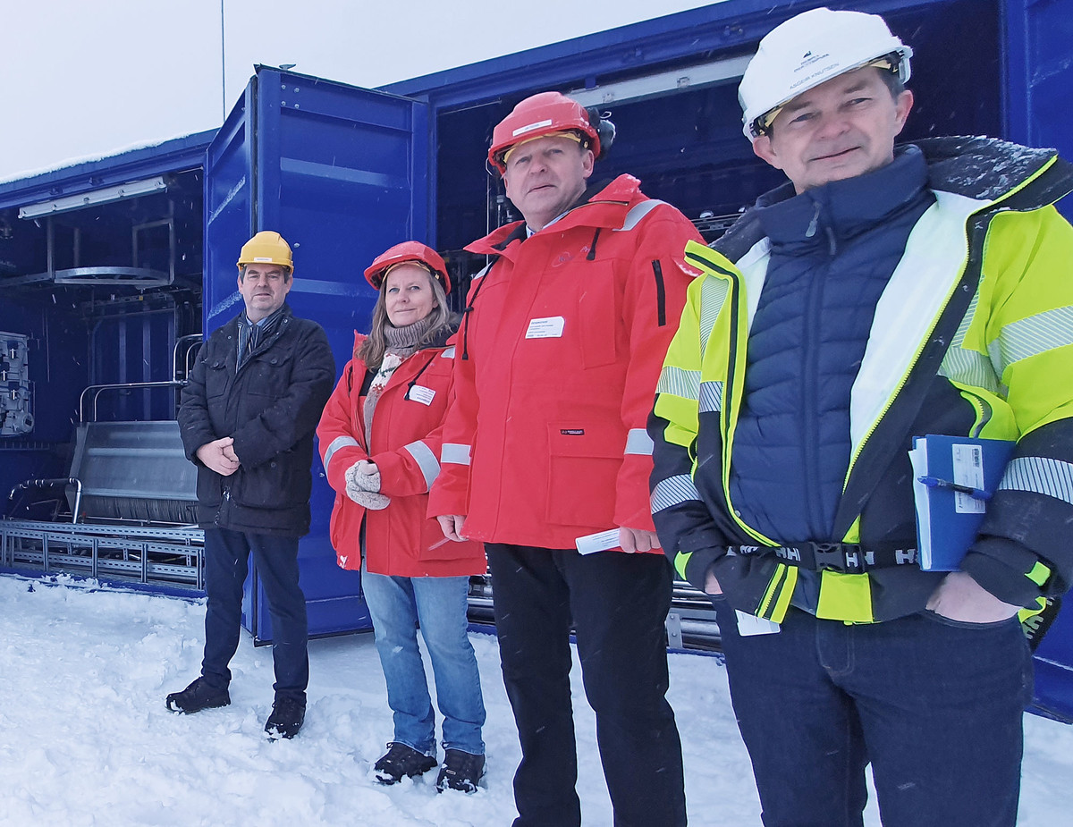 four persons out in the snow dressed in bid work clothes and helmets