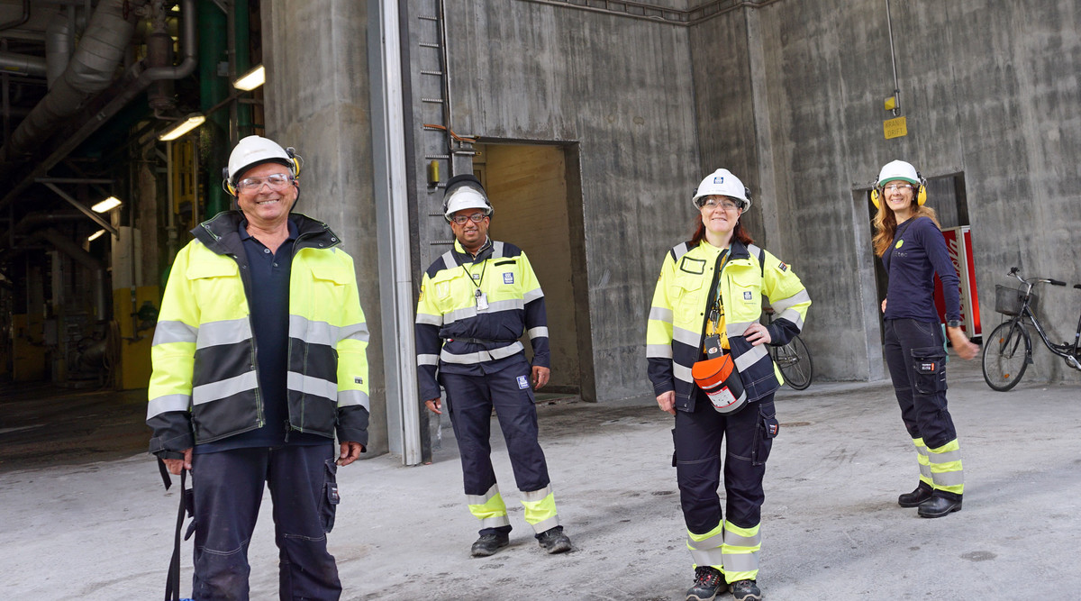 four persons dressed in yellow and blue working clothes standing in grey concrete production hall