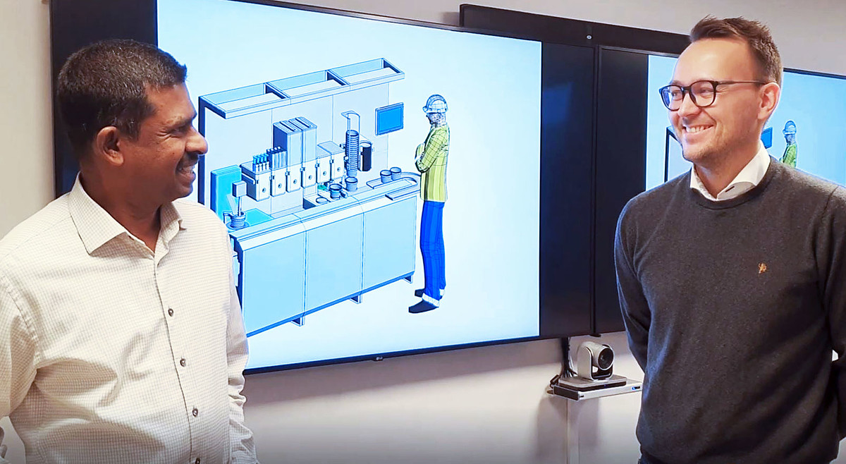 two men in front of a monitor displaying an animation