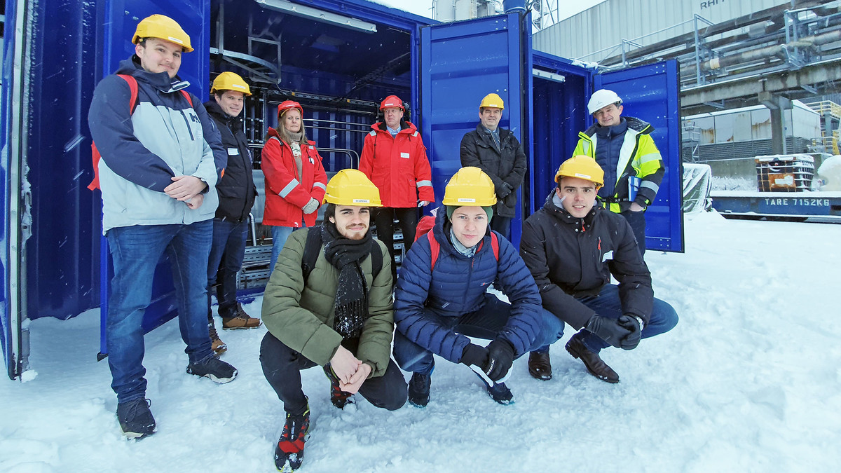 group of nine persons in the snow in front of blue container